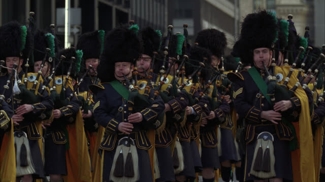 medium angle of bagpipers and soldiers marching in street for military funeral. hearse and police escort follow. flashing lights or bizbars visible. flags. funeral processions. - bagpipes stock videos & royalty-free footage