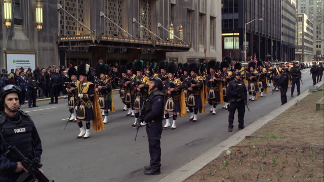 wide angle of parade or military funeral procession with armed police officers controlling crowd on sidewalk as bagpipers march down street. flags. waldorf astoria hotel in bg. - ウォルドルフ・アストリア点の映像素材/bロール