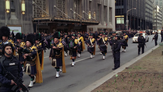 wide angle of parade or military funeral procession with armed police officers controlling crowd on sidewalk as bagpipers march down street. flags. waldorf astoria hotel in bg. police cars with flashing lights or bizbar follow. hearse visible. - ウォルドルフ・アストリア点の映像素材/bロール