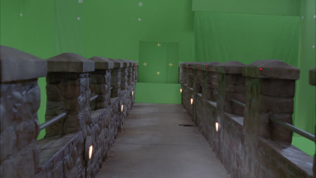 WIDE ANGLE MOVING POV OF WALKING WITH FLASHLIGHT ACROSS STONE BRIDGE WITH BATTLEMENT OR CRENELLATION. ROPE TIED ONTO RAILING. GREEN SCREEN.