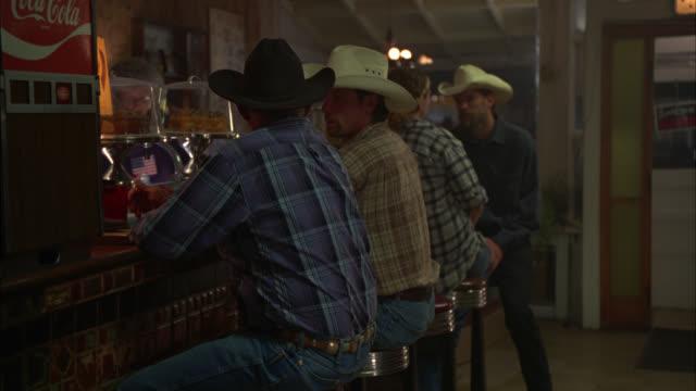 medium angle of men sitting at bar of restaurant or diner wearing cowboy hats. - bar点の映像素材/bロール