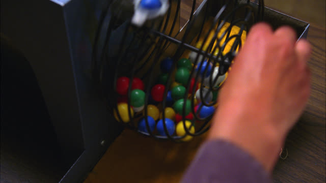 CLOSE ANGLE OF ROTATING BINGO CAGE FILLED WITH COLORED BALLS WITH THE NUMBERS ON THEM. GAMBLING GAMES.