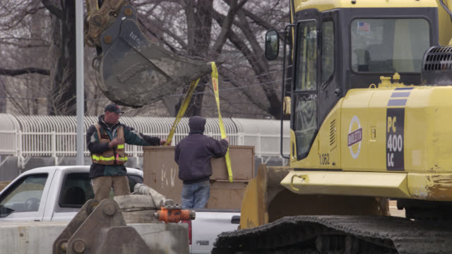 hand held of men working at construction site. backhoe and other construction vehicles, along with concrete beams and lumber. mud and snow on ground. workers. - massachusetts stock videos & royalty-free footage