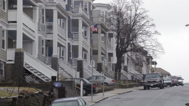 wide angle of neighborhood or residential area street in boston. suburbs. multi-story apartment buildings and houses along street with parked cars with massachusetts license plates. american flag waving from balcony. middle class. - dollhouse stock videos & royalty-free footage