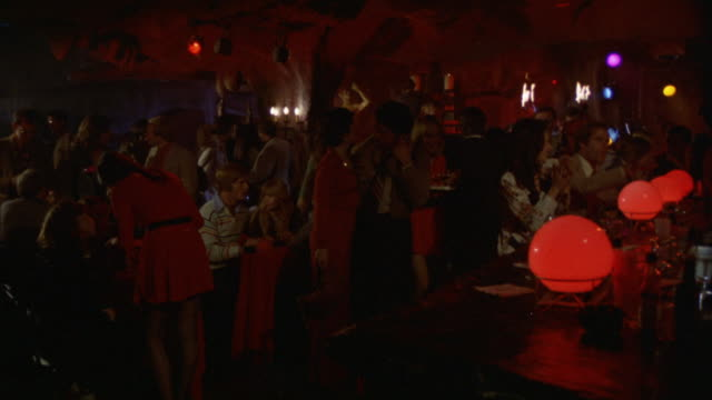 nightclub disco or discotheque. crowd of  people. (watch principals seated at tables). trim audience. - anno 1975 video stock e b–roll