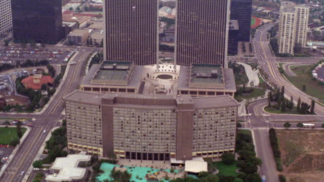 aerial pov down to century city hotel. swimming pool. buildings  (office). beyond a-g. - century city stock videos & royalty-free footage