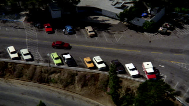 aerial in hazy weather to establish griffith observatory. red car leaves parking lot. - anno 1985 video stock e b–roll