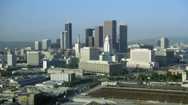stockvideo's en b-roll-footage met aerial of los angeles skyline. police astro division station department. helicopters on roof.  downtown los angeles. - 1983