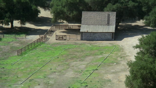 aerial over green trees pine country farm land open countryside. see ranch house or cabin or lodge from air country side empty corral. pan over steps to ranch house. - ranch stock videos & royalty-free footage