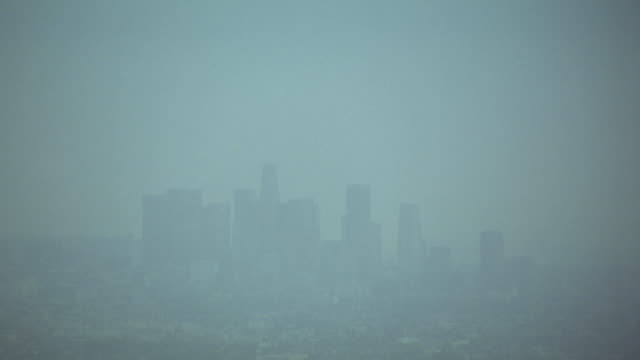aerial view of los angeles city skyline behind smog. skyscrapers or high rise buildings in background. see hazy sky. buildings of business district or residential area below. see pan out to century city twin towers behind abc entertainment center in foreg - century city stock-videos und b-roll-filmmaterial