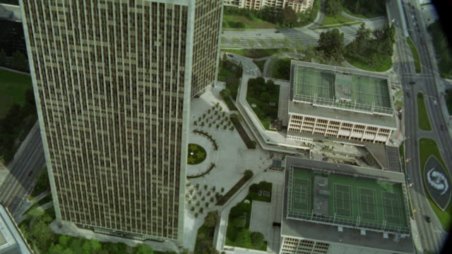aerial view of century city twin towers behind abc entertainment center and surrounding area. see various trees, streets cars, office buildings, and apartment buildings in surrounding community, neighborhood, or residential area. - century city stock videos & royalty-free footage