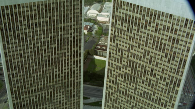 aerial view of century city twin towers behind abc entertainment building and surrounding area. see various trees, streets cars, office buildings, and apartment buildings in surrounding community, neighborhood, or residential area. - century city stock videos & royalty-free footage
