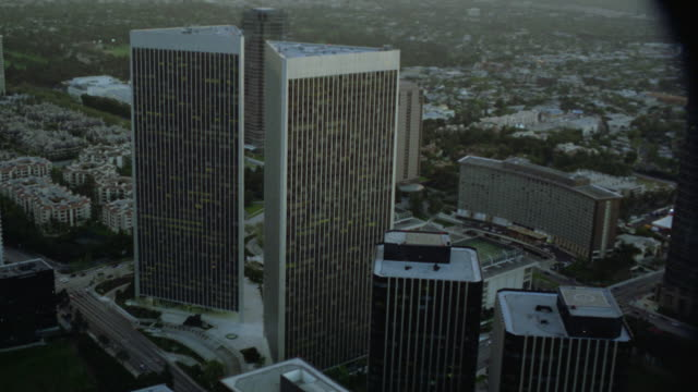"aerial view of century city twin towers behind abc entertainment center and surrounding area. see one multi-story building read ""sun america."" see various office buildings, apartment buildings, streets, houses, and cars in residential or community area. - century city stock-videos und b-roll-filmmaterial"
