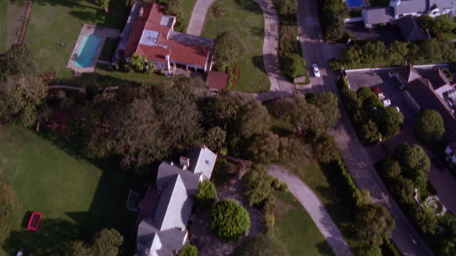 stockvideo's en b-roll-footage met aerial view of beverly hills residential or neighborhood area. see various houses, homes and mansions. see tennis courts and swimming pools in some backyards. see large green trees, grass fields and other vegetation. see pov pan up to view high rise build - beverly hills californië