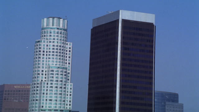 stockvideo's en b-roll-footage met aerial of downtown los angeles city skyline. high rises and skyscrapers. glass office buildings and us bank tower. camera tilts down to high angle down of city streets and parking lots. - us bank tower