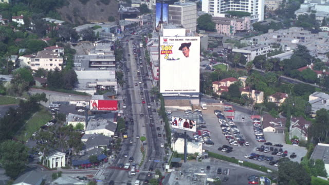 "aerial of sunset blvd and sunset strip. buildings and office buildings. high rises. building posters of lucille ball and desi arnaz. ""toy story 2."" camera travels east. chateau marmont hotel. vehicles driving on street below. - sunset boulevard stock-videos und b-roll-filmmaterial"
