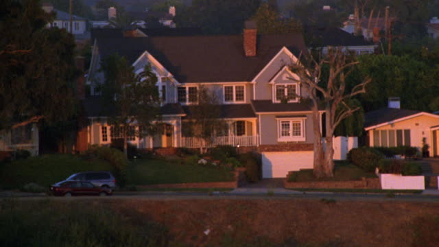 aerial of upper class two story house located on cliff or bluff. coastal or ocean side. suv drives past house on coastal road while silver suv pulls into driveway. camera pulls back and up to high angle down of roofs of houses or homes in neighborhood.<p> - zweistöckiges bauwerk stock-videos und b-roll-filmmaterial