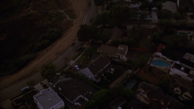 aerial of upper class coastal neighborhood. camera pans around to face upper class two story house located on cliff or bluff. high angle down of silver suv in driveway. ocean and beach in bg. could be malibu or santa monica. - santa monica house stock videos & royalty-free footage