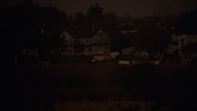 "aerial of upper class two-story house on bluff or cliff. trees and vegetation. upper class suburban neighborhood. camera pulls back as white suv pulls out of driveway and drives away down street. coast. could be santa monica or malibu.<p><a href=""https:// - santa monica house stock videos & royalty-free footage"