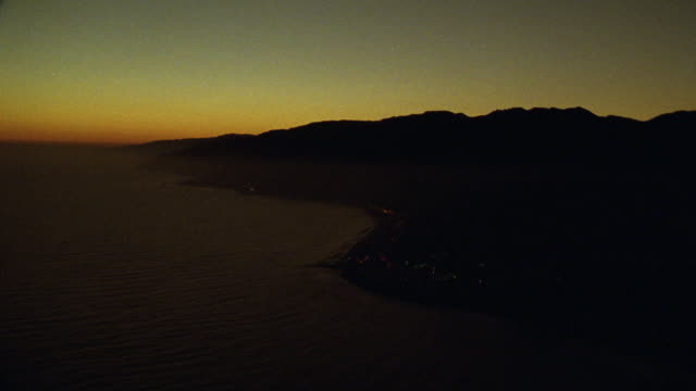 aerial of sunset over coast of malibu. city below. light and streets below. cliffs. - malibu stock videos & royalty-free footage
