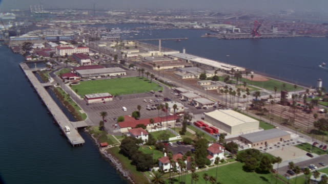 aerial of port of los angeles. terminal island federal prison or federal correctional institute. prison. cranes in bg. camera zooms to freighter or cargo ship assisted by tugboat.  vincent thomas bridge in background. boats in harbor. - island stock videos and b-roll footage