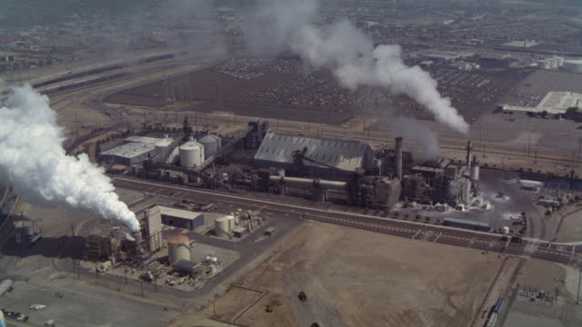 vídeos de stock e filmes b-roll de aerial of port of los angeles. steam or smoke rises from smokestacks of industrial buildings or factory. bp calciner in wilmington, ca, used to convert liquid waste to solids, particularly waste from oil refineries. could be power plant. - wilmington cidade de los angeles