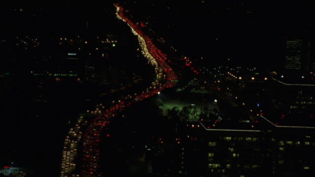 AERIAL OF 405 FREEWAY IN LOS ANGELES NEAR WESTWOOD. BUMPER TO BUMPER TRAFFIC IN BOTH DIRECTIONS. OFFICE BUILDINGS. BASEBALL FIELD ON RIGHT SIDE OF FREEWAY. HEADLIGHTS.