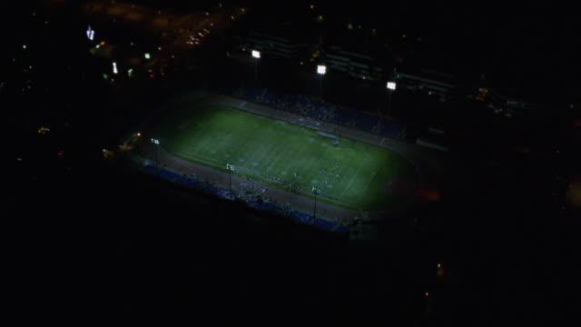 vídeos de stock, filmes e b-roll de aerial approaching lit football stadium. camera zooms in directly over football field. spectators or crowd in stands and players on football field. track surrounding field. - campo de futebol americano