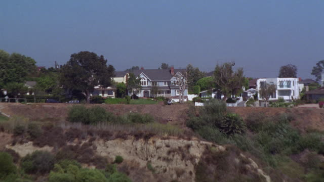 aerial, pan up from ocean to upper class two-story house on cliff or bluff.  aerial. could be coast at malibu or santa monica. runner or joggers jogs by house. white suv parked in driveway. camera pans up to high angle down over house. pool in backyard. r - santa monica house stock videos & royalty-free footage