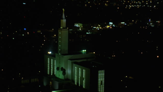 aerial of mormon temple of los angeles on santa monica blvd. city lights in bg. - mormon temple stock videos and b-roll footage