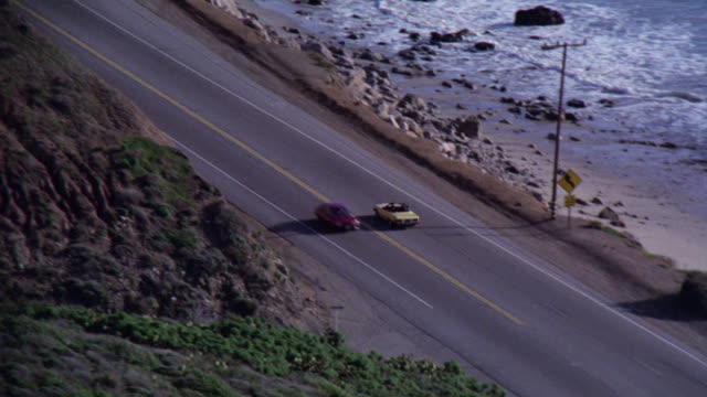 pan left to right of los angeles coastline. camera follows yellow mercedes 450 sl convertible with top down. ocean and cliffs or bluffs. - convertible stock videos & royalty-free footage