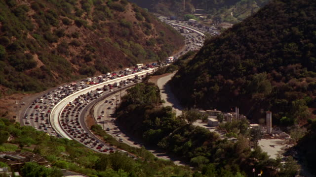 AERIAL OF TRAFFIC ON 405 FREEWAY OR HIGHWAY IN LOS ANGELES. CARS DRIVING. GETTY CENTER ON HILLTOP ABOVE FREEWAY. CITY IN BG. ART MUSEUMS. TREES, HILLS AND MOUNTAINS.