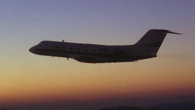aerial air-to-air tracking shot of commercial jet. dusk,  silhouette. - air to air shot stock videos & royalty-free footage