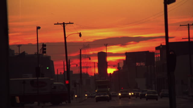 PULL BACK FROM SUNRISE OR SUNSET BEYOND BUILDINGS OF LOS ANGELES. POLICEMAN WALKS TOWARDS SUNSET. 1970'S CAR ON STREET.