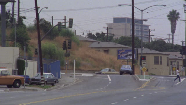 pan right to left as police car drives by two men. red lights near sunset blvd. - sunset boulevard stock-videos und b-roll-filmmaterial