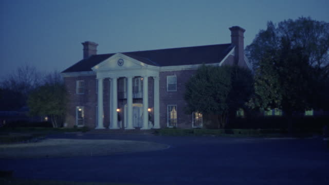"wide angle of colonial or southern style, two-story red brick house or mini mansion with white pillars. could be small estate. lawn and driveway in front yard. roundabout. trees surrounding house.<p><a href=""https://www.sonypicturesstockfootage.com/footag - brick house stock videos & royalty-free footage"