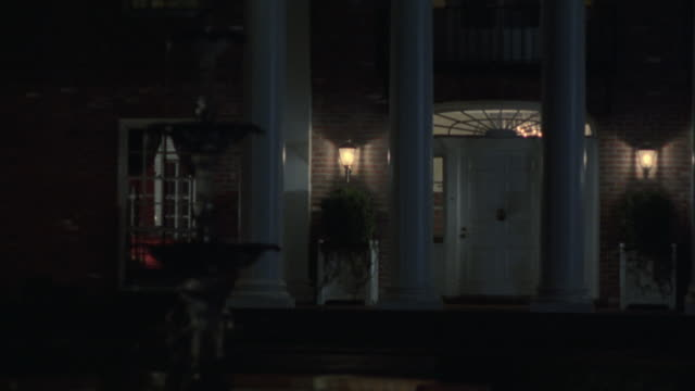 "close angle of colonial or southern style, two-story red brick house or mini mansion with white pillars. could be small estate. lights coming from windows. fountain out of focus in fg.<p><a href=""https://www.sonypicturesstockfootage.com/footage?kid=4314""> - brick house stock videos & royalty-free footage"