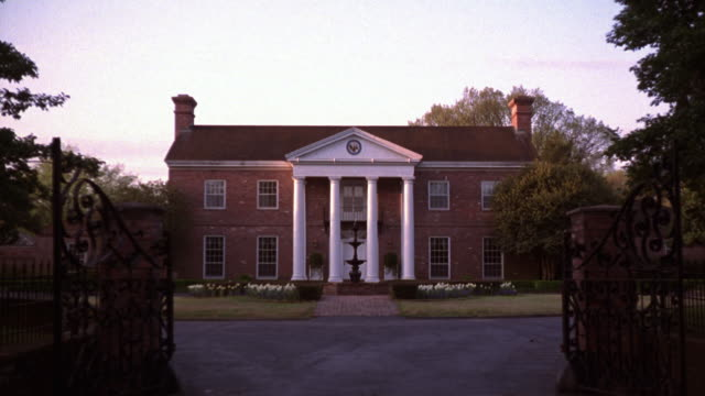 wide angle of colonial or southern red brick two-story house with white pillars. could be mansion or small estate. wrought iron gate or fence in certain shot. fountain in certain shots. driveway and lawns. trees surround property. multiple takes. dusk. bl - mansion stock videos & royalty-free footage