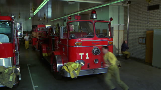 wide angle of firemen, fire fighters going down pole to their stations (was originally 7608). fire stations. - 1982 stock videos and b-roll footage
