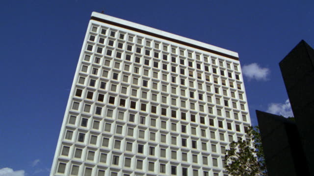 vídeos de stock, filmes e b-roll de pan down fourteen floor, ocd  building (occupation control division). ls up angle  against sky. pan down to entrance level. include street traffic in fg. - entertainment occupation