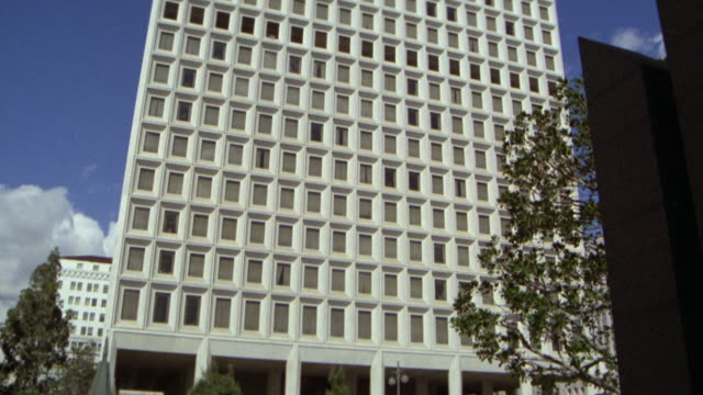 vídeos de stock, filmes e b-roll de pan up fourteen floor, ocd  building (occupation control division). ls up angle  against sky. pan down to entrance level. include street traffic in fg. - entertainment occupation