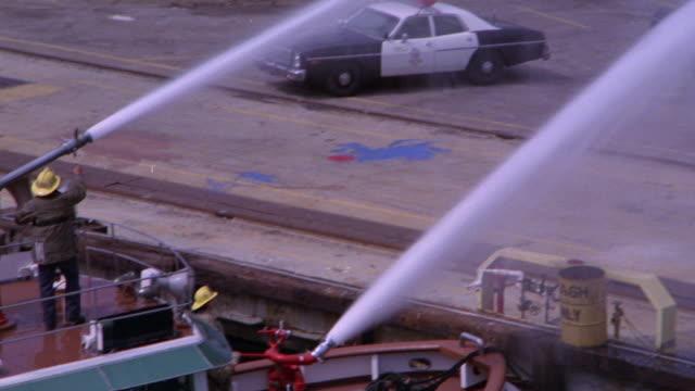 PAN LEFT TO RIGHT OF FIRE BOAT WITH WATER CANNON SPRAYING WAREHOUSE. FIRE OR FLAMES SPEW FROM BUILDING. HOOK AND LADDER, FIRE TRUCKS, NEWS VANS, AND FIREMEN OR FIREFIGHTERS BELOW. WATER HOSES.