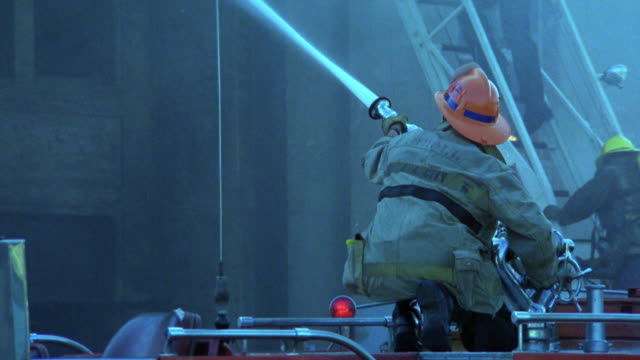 stockvideo's en b-roll-footage met medium angle of firemen on ladder spraying water from hose at multi-story apartment building to put out fire. - fire hose