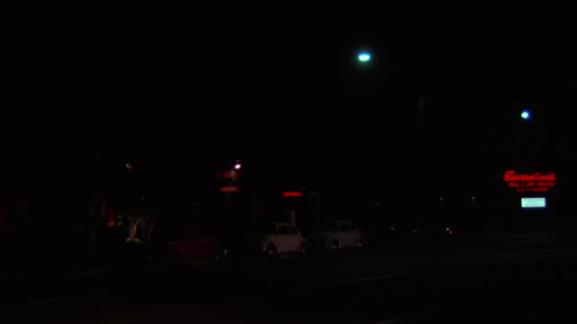 pan right to left of brown car driving and then making a u-turn. stores and motel in bg in commercial area. - motel stock videos & royalty-free footage