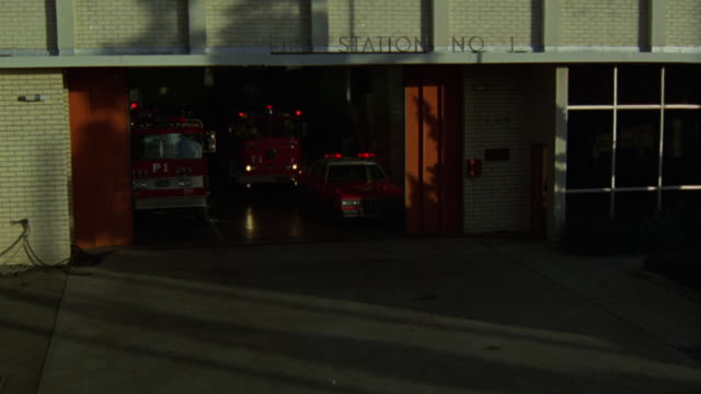 pan left to right from fire station 1, white brick building with orange doors. doors open and two fire trucks and fire chief's car drive away. emergencies. - fire station stock videos & royalty-free footage