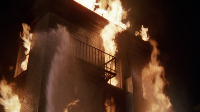 wide angle of condemned 3 story brick building on fire. hoses with water streams trying to put fire out. deserted. flames from windows. fire escape. neg cut. two firefighters. - 1982 stock videos and b-roll footage