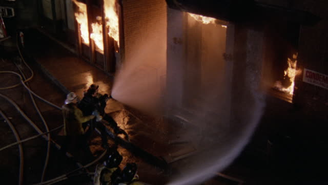 vídeos de stock e filmes b-roll de high angle down of condemned 3 story brick building on fire. hoses with water streams trying to put fire out. deserted. flames from window. down angle to firemen spraying water on fire. - mangueira