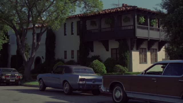 wide angle of two story middle class apartment building. spanish red tile roof. tree out front. old blue ford mustang convertible and station wagon parked on street. - mustang convertible stock videos & royalty-free footage
