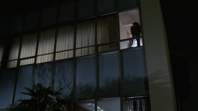 up angle to office or apartment building.  man with cowboy hat and gun in right hand falls backwards out of glass window. broken windows.  stunt shot same as 1311-g - 1987 bildbanksvideor och videomaterial från bakom kulisserna