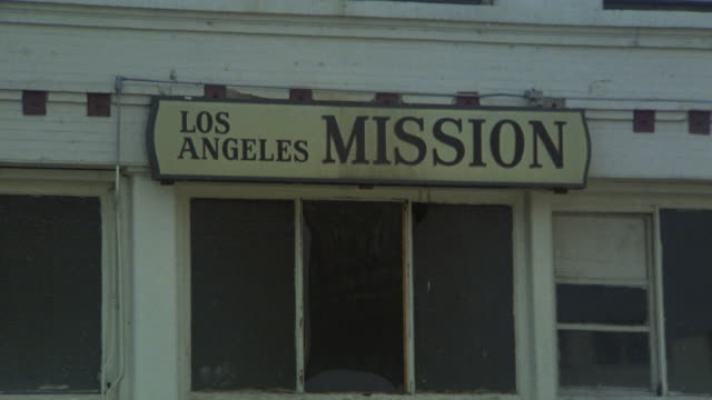 "pull back from ""los angeles mission"" sign to exterior or entrance of homeless shelter. people lie on street and stand in front of brick building. lower class urban area downtown. cars drive down street. - homeless shelter stock videos & royalty-free footage"
